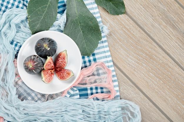 Um prato de figos pretos inteiros e fatiados, uma folha e toalhas de mesa azuis e rosa na mesa de madeira.