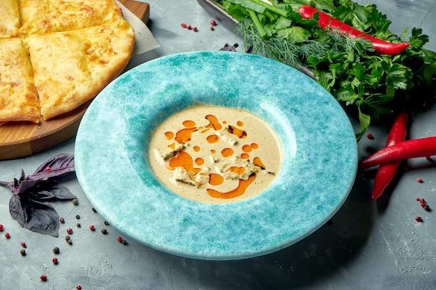 Um prato de filé de frango georgiano com molho de nozes ou satsivi em prato azul com khachapuri. fechar-se