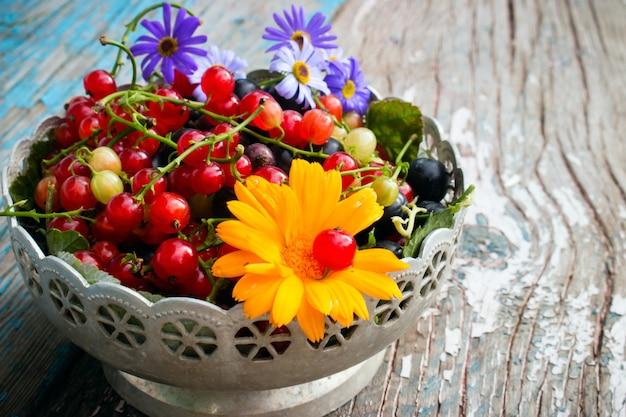 Um prato de folhas e bagas de groselha preta e vermelha com uma flor na madeira