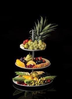 Um prato de frutas exóticas de três andares com frutas mistas.
