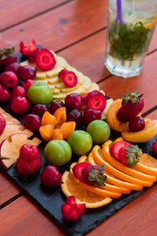 Um prato de frutas exóticas e um copo de mojito