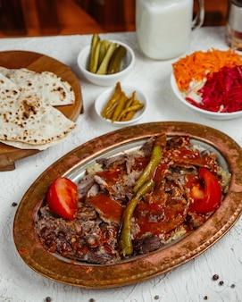 Um prato de kebab de carne coberto com molho de tomate