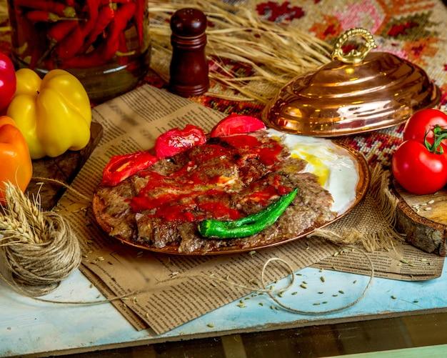 Um prato de kebab de cordeiro turco servido com iogurte tomate e pimenta grelhados