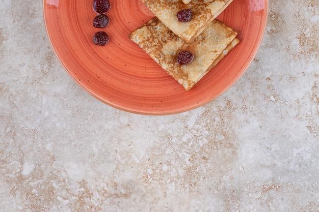 Um prato de laranja com saborosas panquecas finas e frutas vermelhas