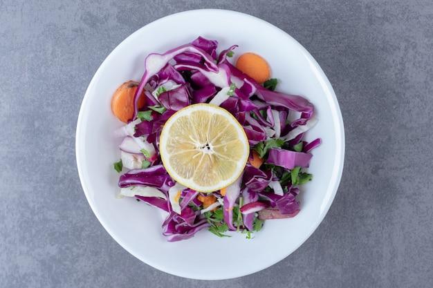 Um prato de legumes ralados com limão, na superfície de mármore.