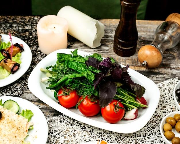 Um prato de legumes verdes com rabanete de pepino de tomate e ervas