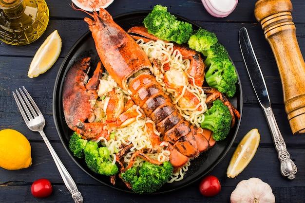 Um prato de macarrão com lagosta de boston no vapor