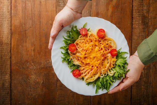 Um prato de macarrão com queijo e tomate cereja em mãos femininas. foto horizontal
