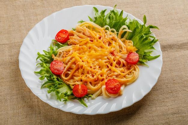 Um prato de macarrão com tomate cereja e queijo sobre uma toalha de mesa de linho.