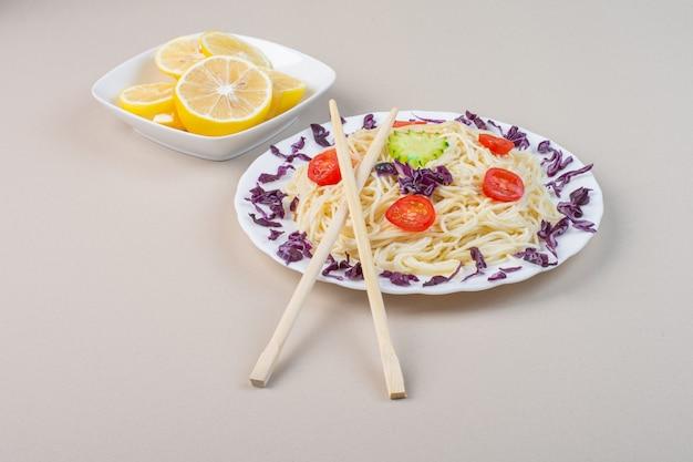 Um prato de macarrão cozido com legumes e limão fresco fatiado.