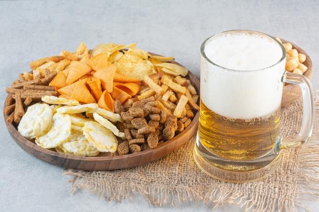 Um prato de madeira cheio de deliciosos peixes e queijos com cerveja e ervilhas.