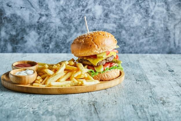 Um prato de madeira cheio de hambúrguer, batata frita com ketchup e maionese na mesa de mármore.