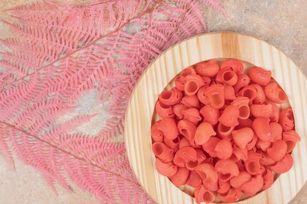 Um prato de madeira cheio de macarrão vermelho não preparado.