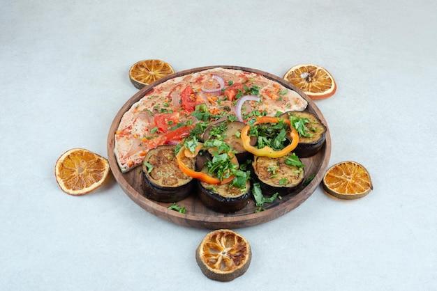 Um prato de madeira cheio de pão sírio com berinjela fatiada.