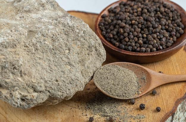 Um prato de madeira cheio de pimenta seca sobre uma superfície branca.