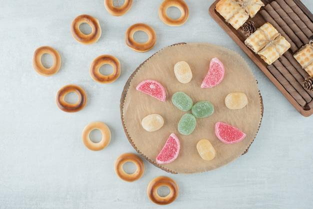 Um prato de madeira com balas de açúcar e biscoitos redondos em fundo branco. foto de alta qualidade