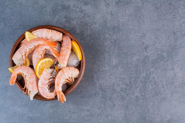 Um prato de madeira com deliciosos camarões com cubos de gelo e limão cortado em uma superfície de pedra