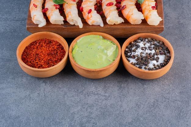 Um prato de madeira com deliciosos camarões com pimenta em uma superfície de pedra