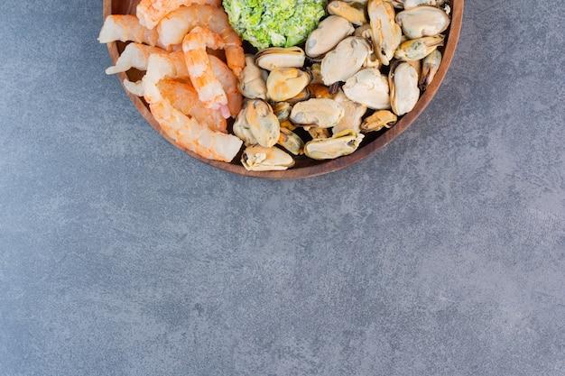 Um prato de madeira com deliciosos camarões com saborosos palitos de caranguejo em uma superfície de pedra
