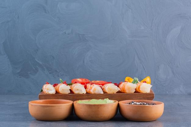 Um prato de madeira com deliciosos camarões com tomate cereja fatiado e pimenta em uma superfície de pedra