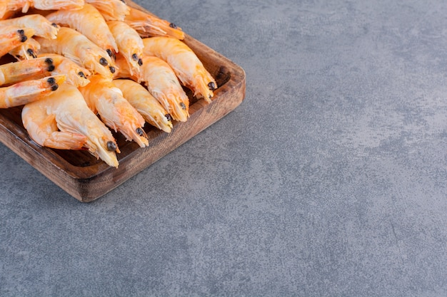 Um prato de madeira com deliciosos camarões em uma superfície de pedra Foto gratuita