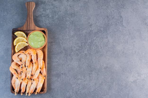 Um prato de madeira com deliciosos camarões em uma superfície de pedra