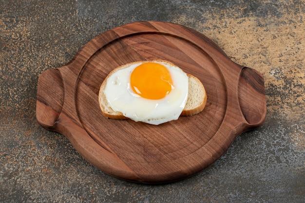 Um prato de madeira com ovo na fatia de pão branco.