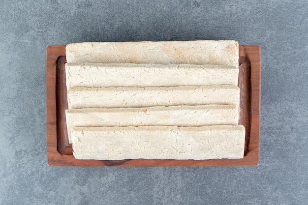 Um prato de madeira com pão de centeio crocante.