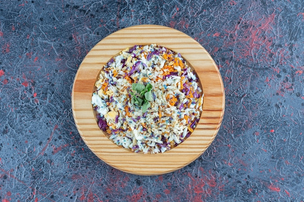 Um prato de madeira com salada de legumes na superfície de mármore