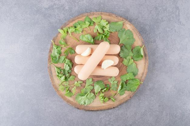 Um prato de madeira com salsichas cozidas com salsa e alho