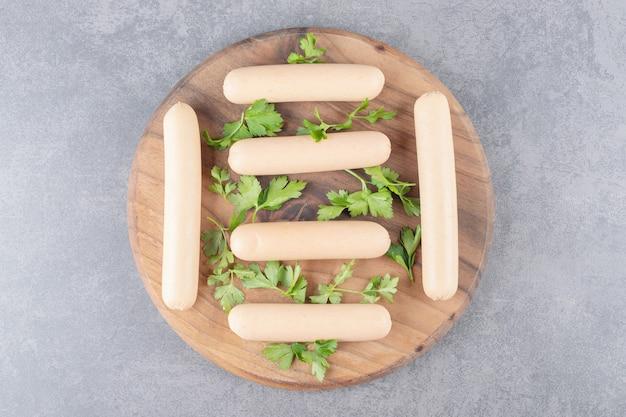 Um prato de madeira com salsichas cozidas com salsa