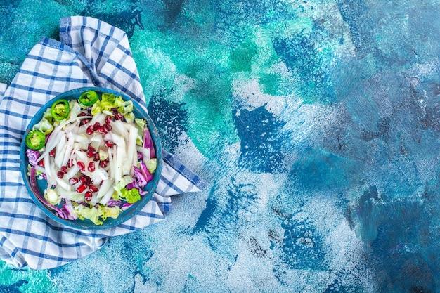 Um prato de madeira com vegetais frescos picados em uma toalha