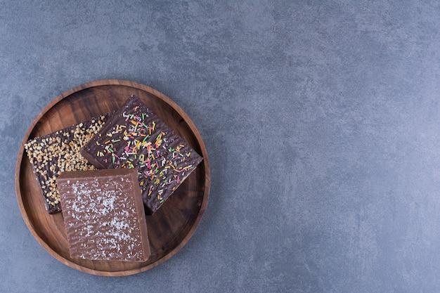 Um prato de madeira com waffle de chocolate picado sobre uma toalha de mesa.