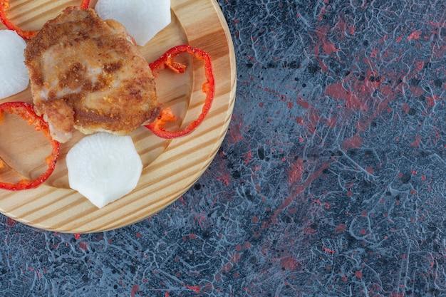 Um prato de madeira de costeleta de frango com pimenta em fatias.