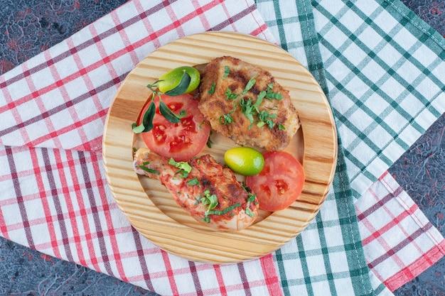 Um prato de madeira de costeleta de frango com tomate fatiado.