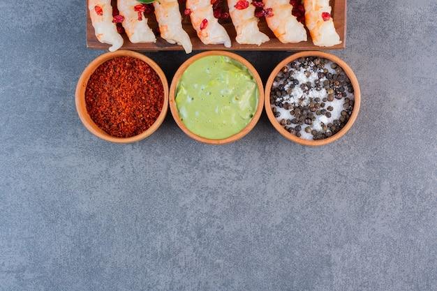 Um prato de madeira de deliciosos camarões com tomate cereja fatiado e pimenta em um fundo de pedra.
