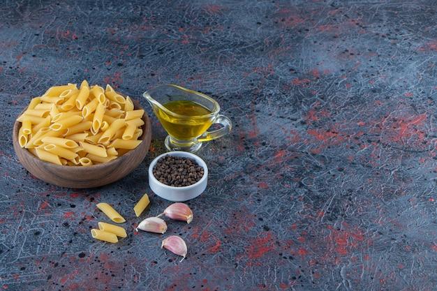 Um prato de madeira de massa crua com grãos de óleo e pimenta em um fundo escuro.