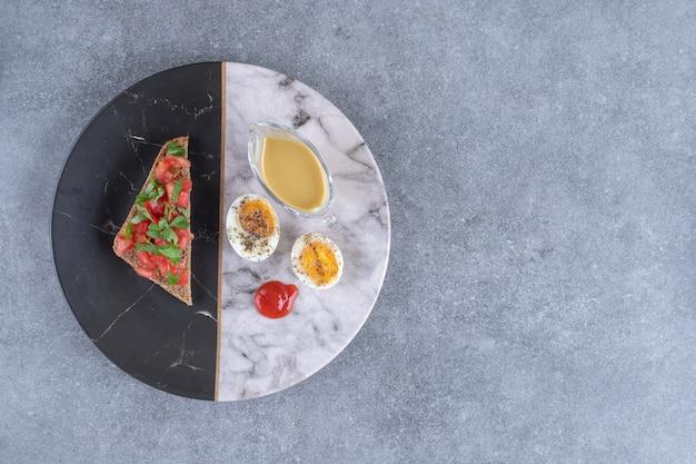 Um prato de mármore com ovo cozido e torradas