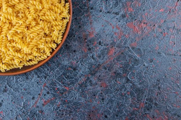 Um prato de massa espiral não cozida com óleo e tomates vermelhos frescos em um fundo escuro.