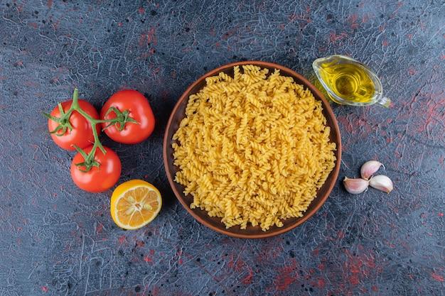 Um prato de massa espiral não cozida com óleo e tomates vermelhos frescos em uma superfície escura.