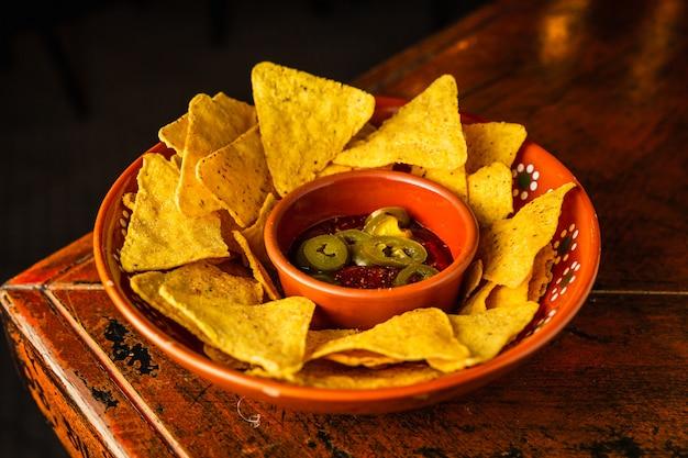 Um prato de nachos com molho de tomate e pimenta jalapeno