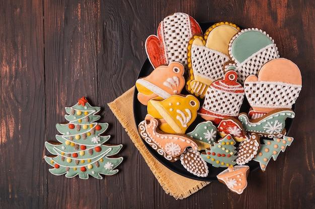 Um prato de natal gingerbread com fundo marrom de madeira, plana leigos.