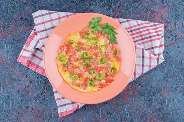 Um prato de omelete rosa com legumes.