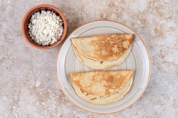 Um prato de panquecas de pão com queijo cottage