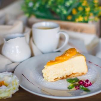 Um prato de pedaço de bolo de queijo decorado com fatias de damasco