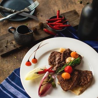 Um prato de pedaços de bife de cordeiro, guarnecido com legumes e alecrim