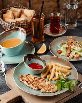 Um prato de peito de frango grelhado servido com batata frita e ketchup