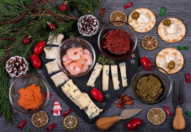 Um prato de queijo escuro com comida italiana e decoração de natal