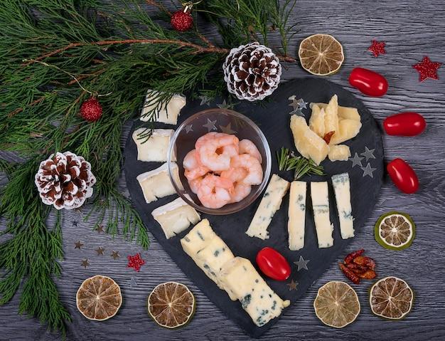 Um prato de queijo escuro com harissa e camarão, parmesão, gorgonzola, alecrim, azeitona e biscoitos