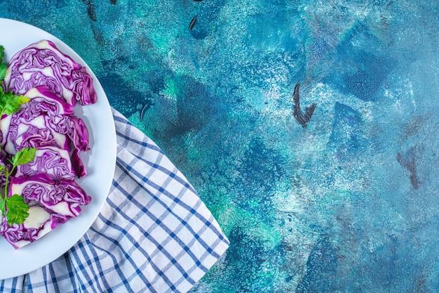 Um prato de repolho fatiado e repolho roxo em uma toalha